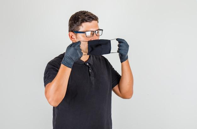 若い医者は黒のポロシャツでマスクを着用