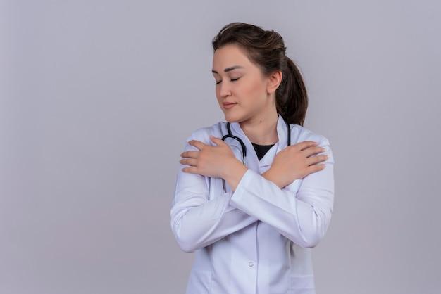 聴診器を身に着けている医療用ガウンを身に着けている若い医者は白い壁の肩に彼女の手を置きます