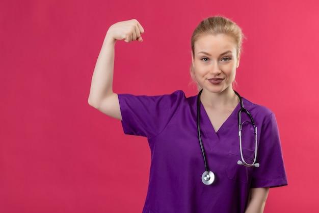 Giovane medico che indossa abito medico viola in stetoscopio facendo un forte gesto sulla parete rosa isolata