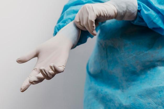 Giovane medico che indossa guanti chirurgici