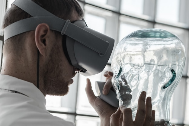 A young doctor wearing vr goggles examining a mannequin in vr simulation - future technology concept