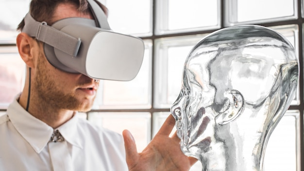 A young doctor wearing vr goggles examining a mannequin in vr simulation