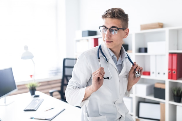 A young doctor in a white robe is leaning on the table in the office he has a phonendoscope around his neck