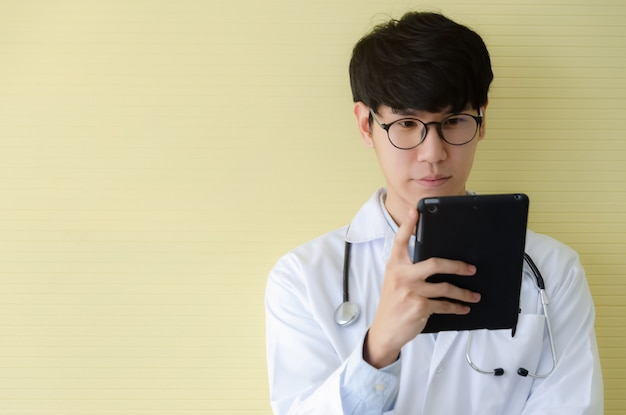 Young doctor in white uniform looking serious at digital tablet