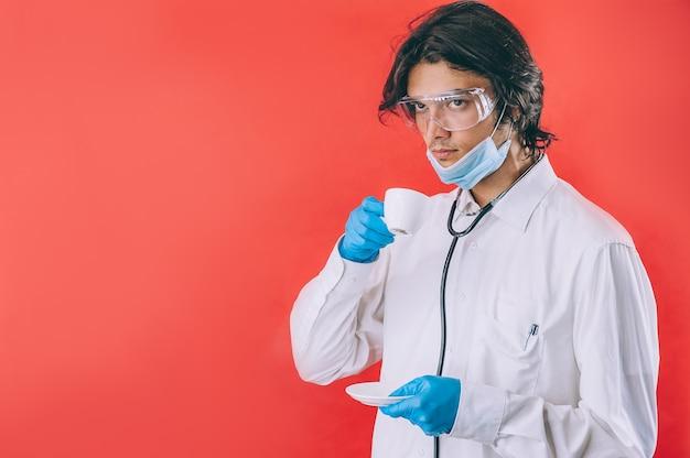 赤いスペースで彼の手にコーヒーのカップを持つ若い医者。