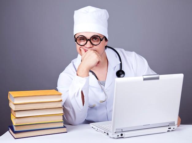 Молодой врач с книгами и компьютером.