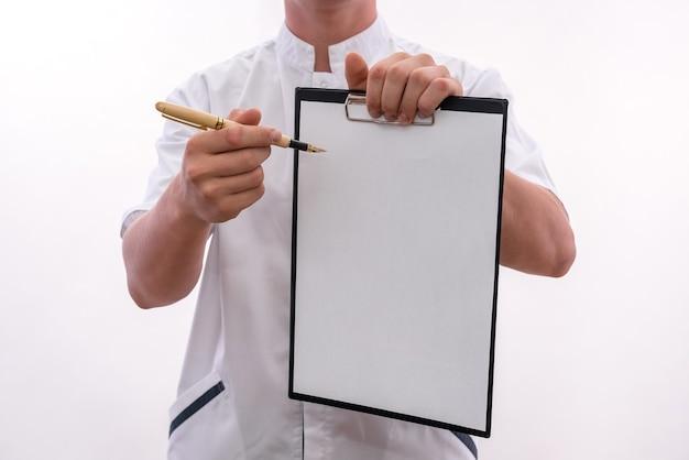 白い壁に分離されたクリップボードとペンを持つ若い医者