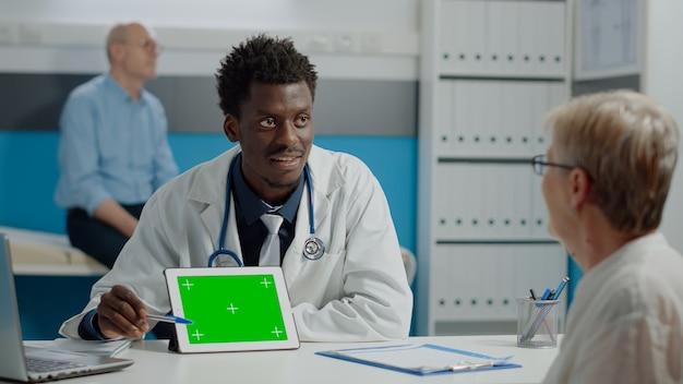 タブレットでグリーンスクリーン技術を持つ若い医者