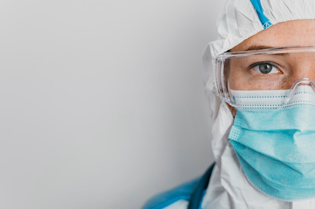 Young doctor with protective equipment with copy space
