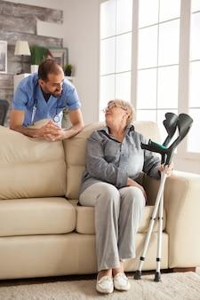 요양원에서 청진기를 들고 수석 여자와 이야기하는 젊은 의사.