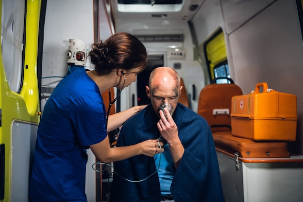 A young doctor with a stethoscope is taking care of her injured patient in an ambulance car.