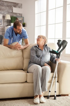 Young doctor with stethoscope in nursing home talking with senior woman.