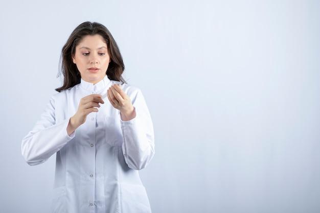 白い壁に注射の準備をしている注射器を持つ若い医者。