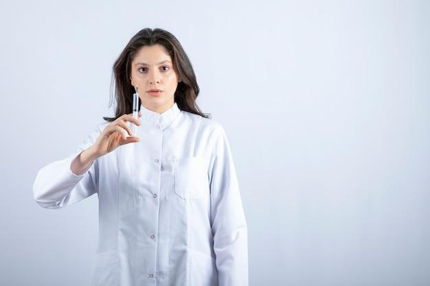 흰 벽에 주사기가 서 있는 젊은 의사.