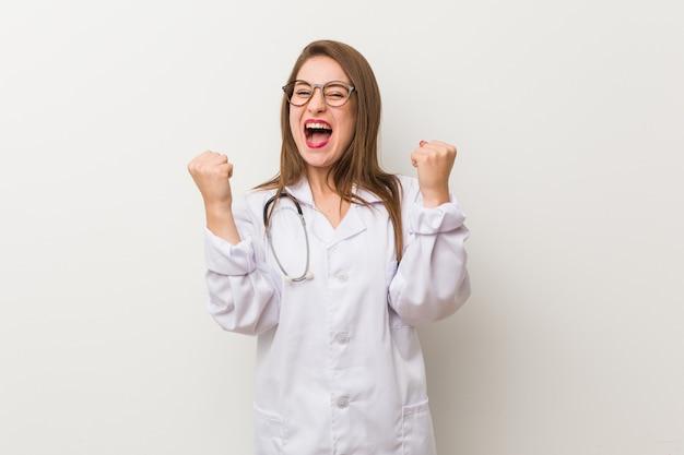 Молодая женщина-врач против белой стены аплодирует беззаботно и взволнованно