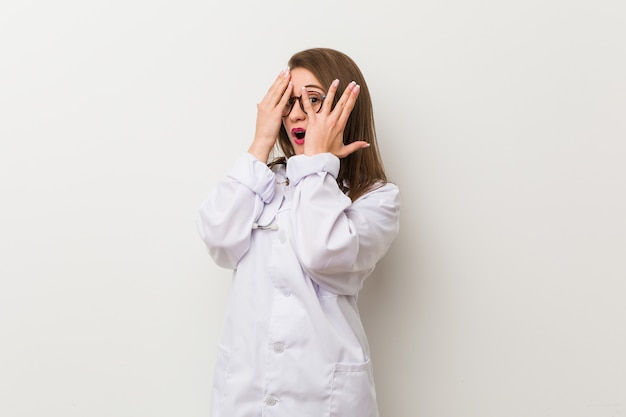 Young doctor woman against a white wall blink through fingers frightened and nervous