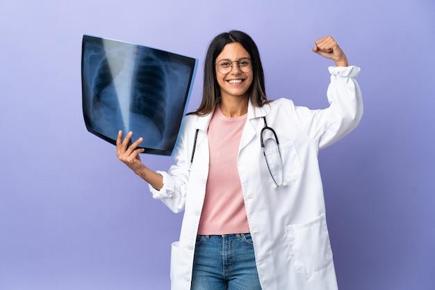 強いジェスチャーをしているレントゲン写真を保持している若い医者の女性
