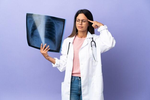 疑いと思考を持っているレントゲン写真を保持している若い医者の女性