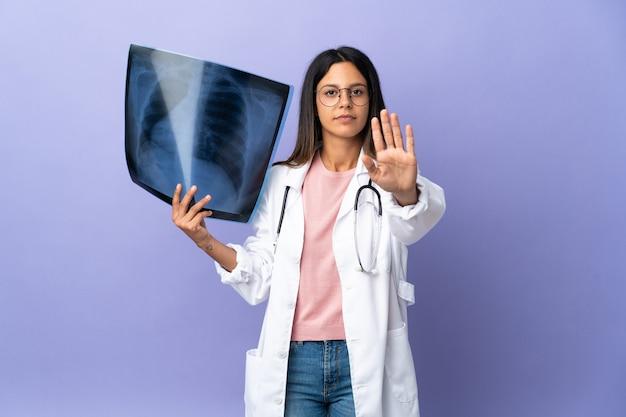 停止ジェスチャーを作るレントゲン写真を保持している若い医者の女性
