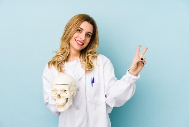 頭蓋骨を保持している若い医者女性は指で平和のシンボルを示すうれしそうな、のんきな分離しました。