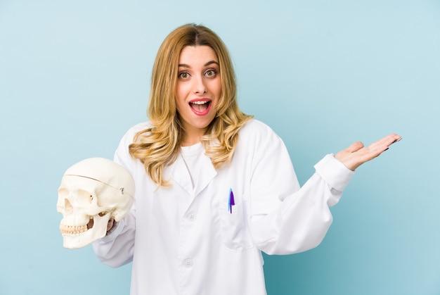 分離された頭蓋骨を保持している若い医者女性は嬉しい驚きを受け取って、興奮し、手を上げます。