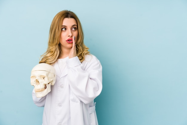 Young doctor woman holding a skull is saying a secret and looking aside