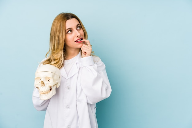 Young doctor woman holding a skull isolated relaxed thinking about something looking at a copy space.