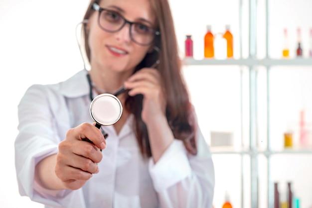 청진기를 통해 듣고 흰색 실험실 코트에 젊은 의사 여자. 친절한 나가는 사교적.