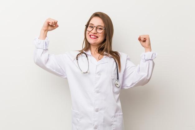 腕、女性の力の象徴と強さのジェスチャーを示す白い壁に若い医者女性