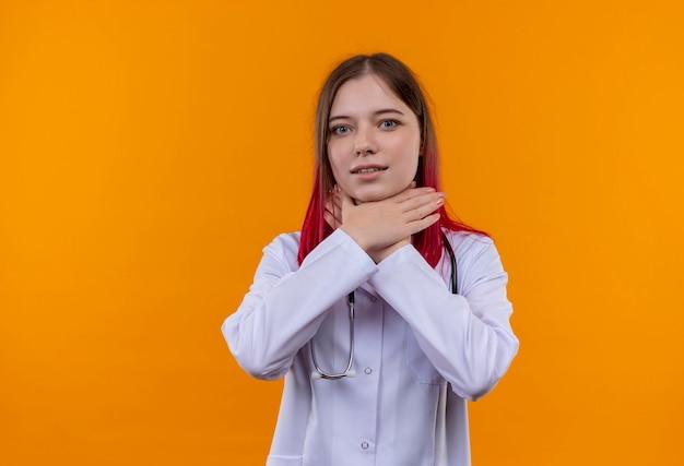 Giovane medico donna che indossa stetoscopio abito medico mettendo le mani sulla gola sul muro arancione isolato