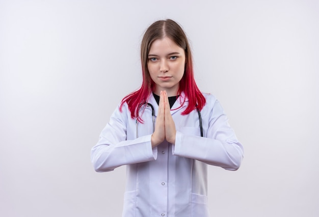 孤立した白い壁に祈りのジェスチャーを示す聴診器医療ローブを身に着けている若い医者の女性