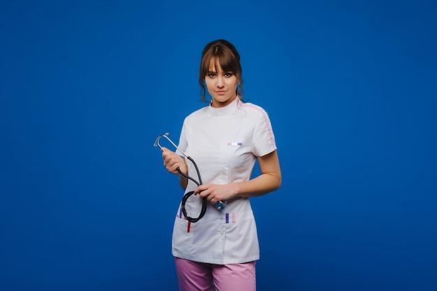 青い背景に分離された聴診器を持つ若い医者の女性。