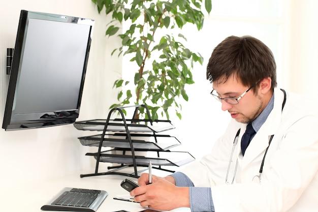 Giovane medico che lavora nel suo ufficio