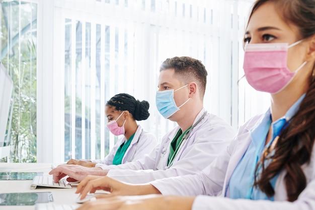 의료용 마스크를 쓴 젊은 의사들이 실험실에서 컴퓨터로 작업하고 환자 데이터와 새로운 백신의 대규모 연구 결과를 입력합니다.