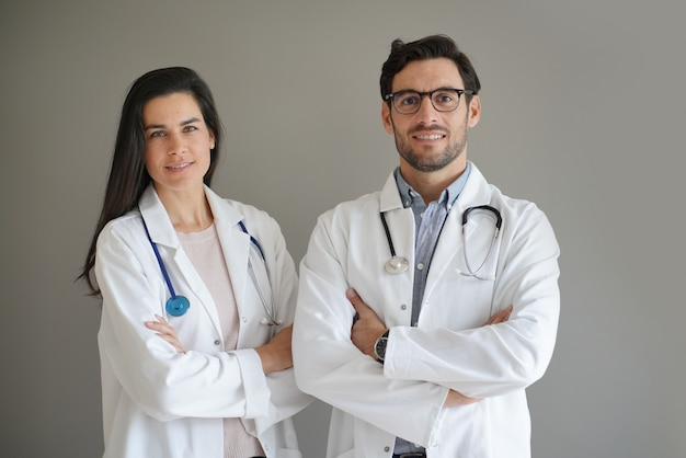 Young doctors in lab coats smiling