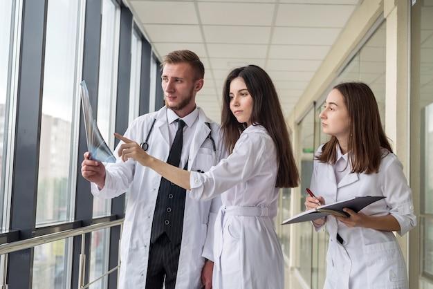 폐의 엑스레이를 보고 있는 젊은 의사들은 코로나바이러스 전염병을 진단합니다. 건강 개념