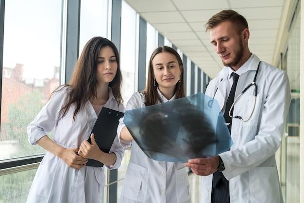 폐 엑스레이를보고있는 젊은 의사들은 코로나 바이러스 전염병을 진단합니다. 건강 개념