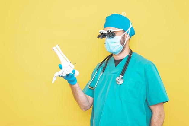Молодой врач-хирург, одетый в зеленое на желтом фоне