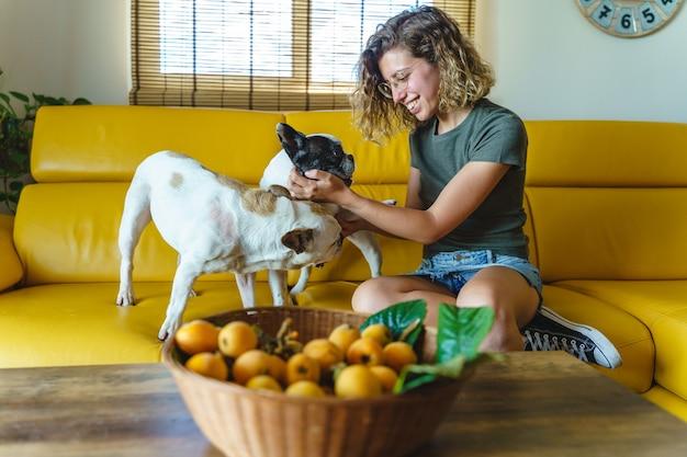 Молодая женщина любитель собак с бульдогом дома. горизонтальный вид владельца женского питомца, играющего с собакой.