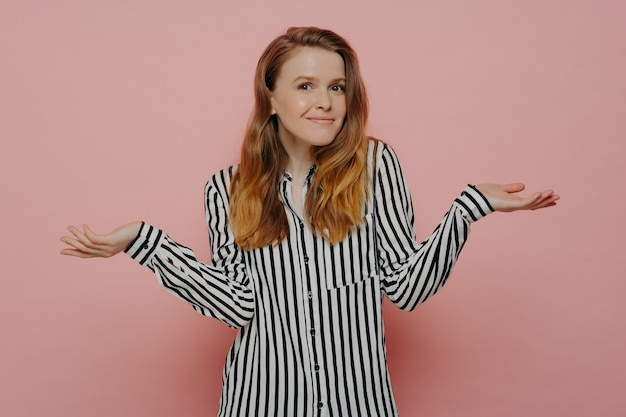 Young doubtful female dressed in white shirt with black stripes, shrugging with both hands in air, doesnt know what to do while stnading next to pink wall in studio. teenage girl looking uncertain