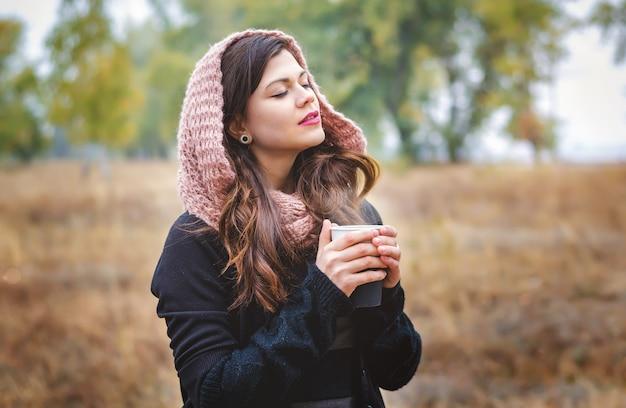 屋外の公園を散歩するためのコーヒー(お茶)を持った若い夢の少女。秋の天気。