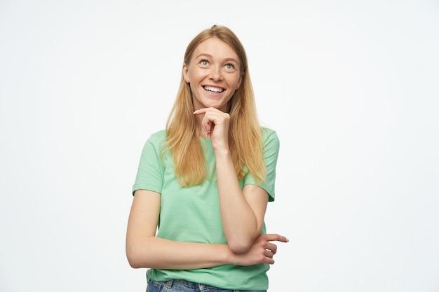 若い夢を見る幸せな女性は緑のtシャツを着ており、デニムジーンズは彼女のあごに触れてスペースをコピーすることに興味があります