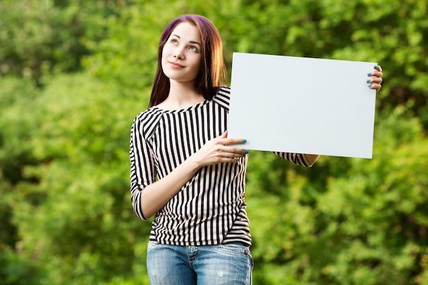 空白の白いバナーを示す若い夢の女性