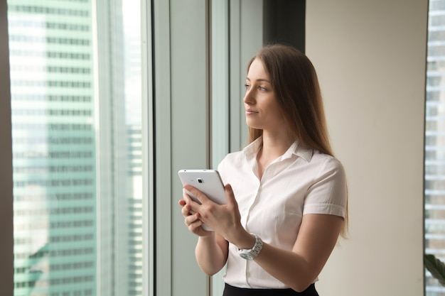 Young dreamy beautiful businesswoman looking through window while holding tablet