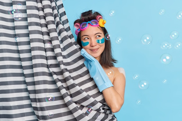 Young dreamy brunette woman with smooth skin applies beauty patches under eyes looks gladfully aside touches face gently applies moisturizing patches under eyes wear rubber glove takes shower