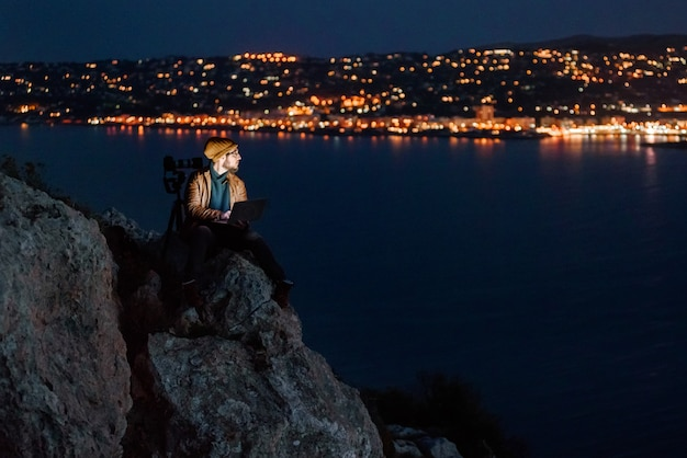 Young dreamy photographer sitting on precipice and working on laptop with view of sea and mountains