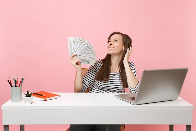꿈꾸는 듯한 젊은 여성은 많은 달러를 들고 있는 것을 올려다보고, pc 노트북이 있는 흰색 책상에서 현금으로 일합니다.
