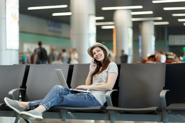 Young dreamy traveler tourist woman working on laptop, talk on mobile phone, call friend, booking taxi, hotel wait in lobby hall at airport