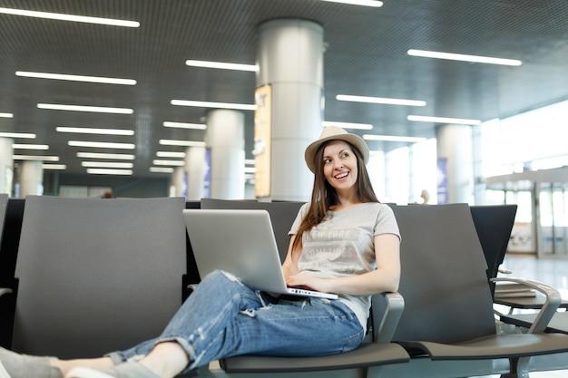 ラップトップに取り組んで、見上げて、国際空港のロビーホールで待っている若い夢のような旅行者観光客の女性