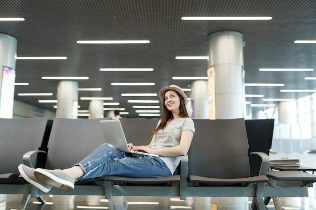 Молодой мечтательный путешественник турист женщина, работающая на ноутбуке, глядя вверх, ожидая в холле вестибюля в международном аэропорту